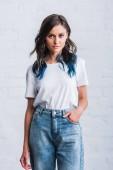 Selektivní fokus mladá žena v prázdné bílé tričko před cihlová zeď