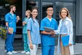 s úsměvem učitel a multikulturní studenti při pohledu kamery na lékařské univerzitě