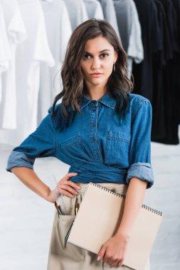 female fashion designer holding textbook in clothing design studio