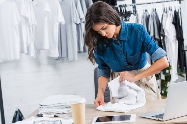 female fashion designer folding t-shirt at table with coffee and digital devices in clothing design studio