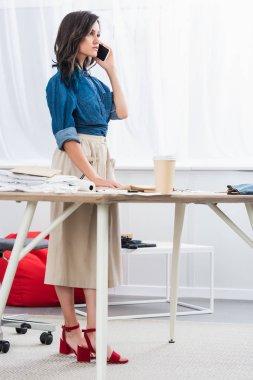 female fashion female fashion designer talking on smartphone in clothing design studio