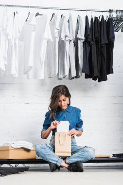 female designer putting white t-shirt in paper bag in fashion design studio