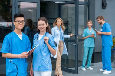 teacher opening doors, multicultural students standing on yard of medical university