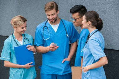 multicultural medical students looking at smartphone at medical university