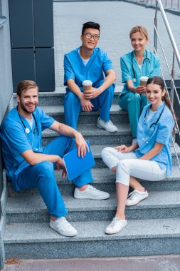 smiling multicultural medical students sitting on stairs and looking at camera