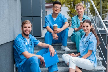 happy multicultural medical students sitting on stairs and looking at camera