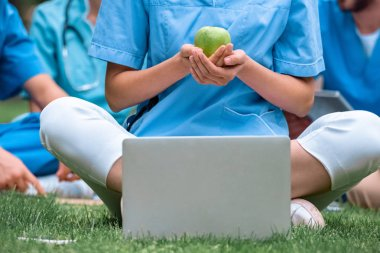 cropped image of medical student holding ripe green apple in hands and sitting near laptop