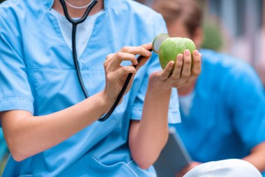 cropped image of medical student examining apple with stethoscope