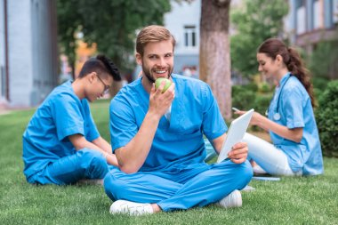 handsome caucasian medical student eating apple and holding tablet
