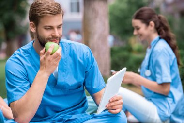 handsome caucasian medical student eating apple and looking at tablet