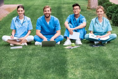 smiling multicultural medical students sitting on grass and looking at camera
