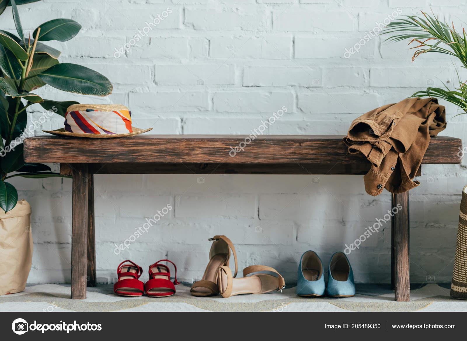7faf8f2891 Διαφορετικά Παπούτσια Κάτω Από Ξύλινο Πάγκο Στο Διάδρομο Στο Σπίτι– εικόνα  αρχείου