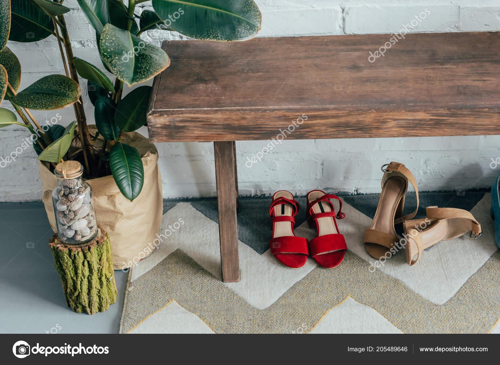 0b1a00cb42 Γλάστρες Διαφορετικά Παπούτσια Κάτω Από Ξύλινο Πάγκο Στο Διάδρομο Στο–  εικόνα αρχείου