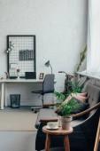Notebook s prázdnou obrazovkou na stůl, pohovku a šálek kávy v moderním obývacím pokoji