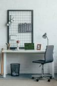 Přenosný počítač s stránky načtené online obchodu na stůl v moderní kanceláři