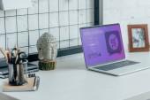 Fotografie Přenosný počítač s načteného web nakupování stránky na stůl v moderní kanceláři