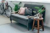 šedá pohovka s polštáři, kolo zdi v obývacím pokoji