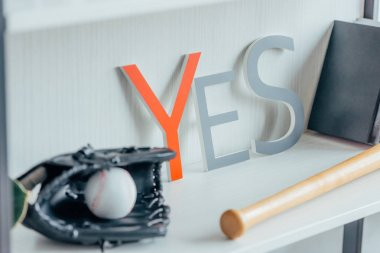 baseball ball, glove and word yes on shelf in office