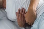 Detailní částečný pohled člověka, který trpí bolestmi žaludku v posteli