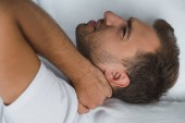 man lying in bed and suffering from pain in neck