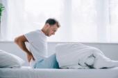 boční pohled mladého muže v pyžamu, sedí na posteli a trpí bolestí zad