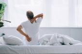vista posteriore di uomo seduto sul letto e soffre di mal di schiena