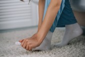 Fotografia ritagliata colpo della donna che ha dolore al piede in camera da letto