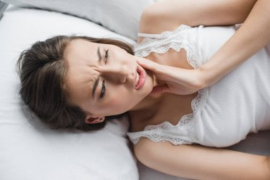 top view of attractive young woman suffering from tooth pain while lying in bed