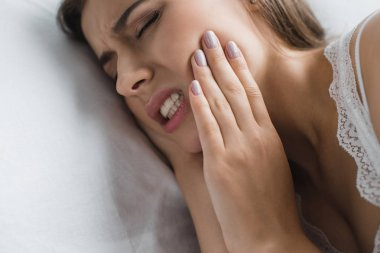 close-up view of young woman suffering from toothache while lying in bed