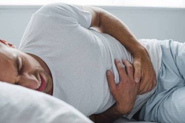 cropped shot of man suffering from stomach pain in bed