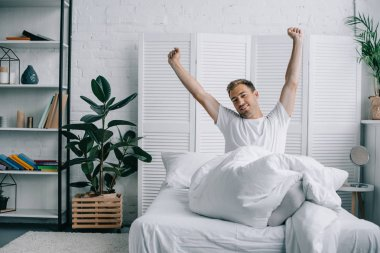 handsome young man stretching hands and smiling at camera in bedroom