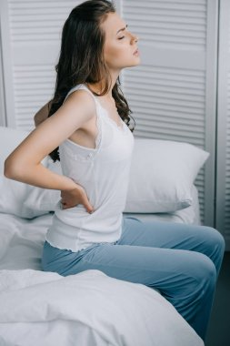 side view of young woman in pajamas suffering from back pain on bed