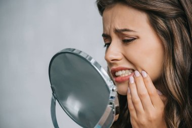 close-up view of young woman having toothache and looking at mirror