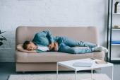 mladý muž ležel na pohovce a trpí bolesti žaludku u vás doma