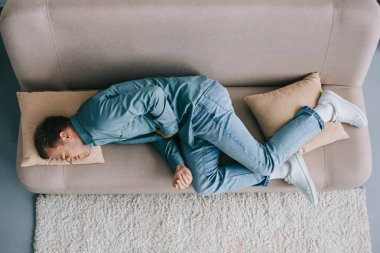 top view of man lying on sofa and suffering from abdominal pain