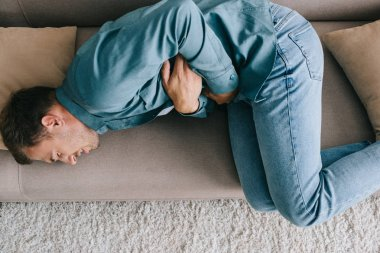 top view of man lying on sofa and suffering from stomach ache