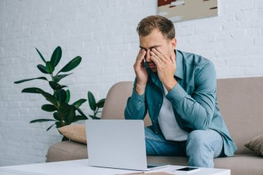 young man rubbing eyes while using with laptop at home