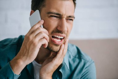 young man talking by smartphone and looking away while suffering from tooth pain at home