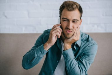 young man talking by smartphone and suffering from jaw pain at home