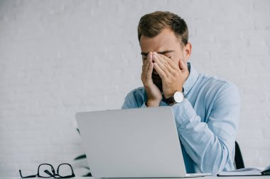 young businessman suffering from pain in eyes while working with laptop
