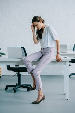 young businesswoman sitting on table and suffering from headache in office