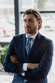 Fotografie pohledný mladý vousatý podnikatel v obleku stojí s překřížením rukou a hledat dál