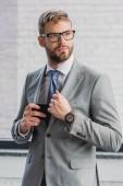 Fotografie pohledný mladý podnikatel v obleku a brýle drží smartphone a hledat dál