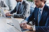 Oříznout záběr koncentrovaného mladých podnikatelů práci s notebooky v úřadu