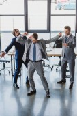 Photo excited young businessmen dancing and celebrating in office