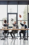 Photo young businessmen throwing balls while working with laptops in office