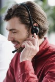 close-up view of smiling young call center operator using headset
