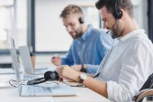 smiling young call center operators in headsets using laptops in office