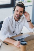smiling young call center operator in headset using laptop in office