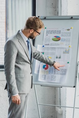 handsome young businessman in suit and eyeglasses pointing at whiteboard with charts and graphs